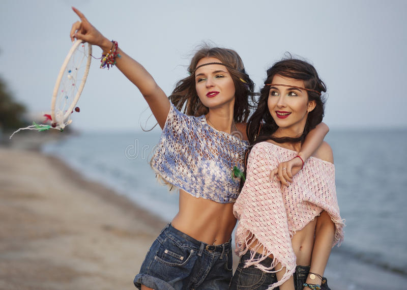 Retrato feliz da mulher do boho de dois jovens no mar que mostra no fotografia de stock royalty free