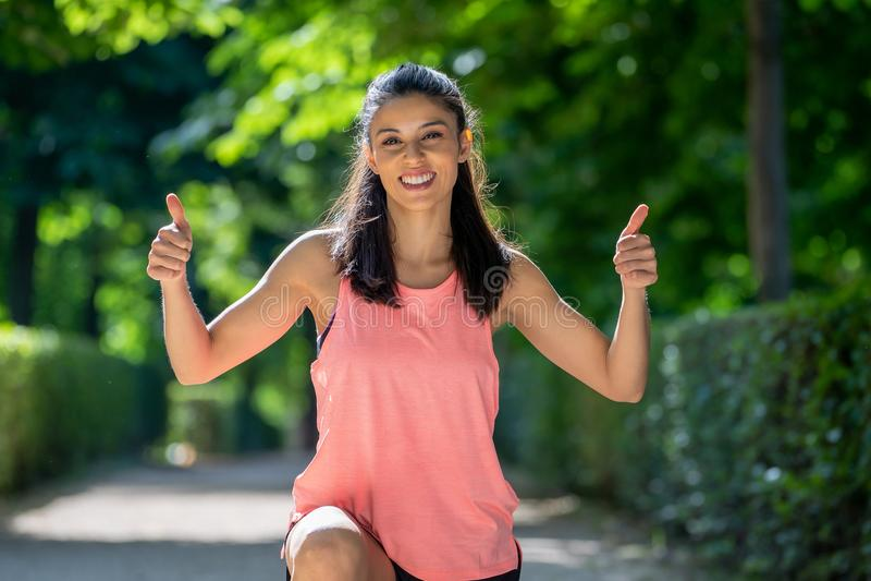 Retrato feliz de la muchacha juguetona que sonríe en la cámara con sus pulgares para arriba imagenes de archivo