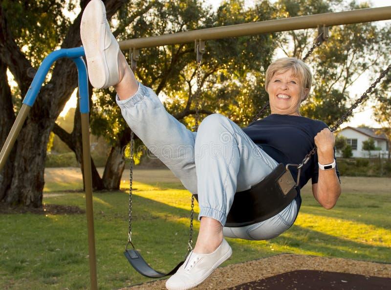Retrato feliz de la mujer hermosa madura mayor americana en su 70s que se sienta en la sonrisa relajada del oscilación del parque imagen de archivo