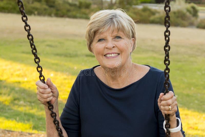 Retrato feliz de la mujer hermosa madura mayor americana en su 70s que se sienta en la sonrisa relajada del oscilación del parque imágenes de archivo libres de regalías