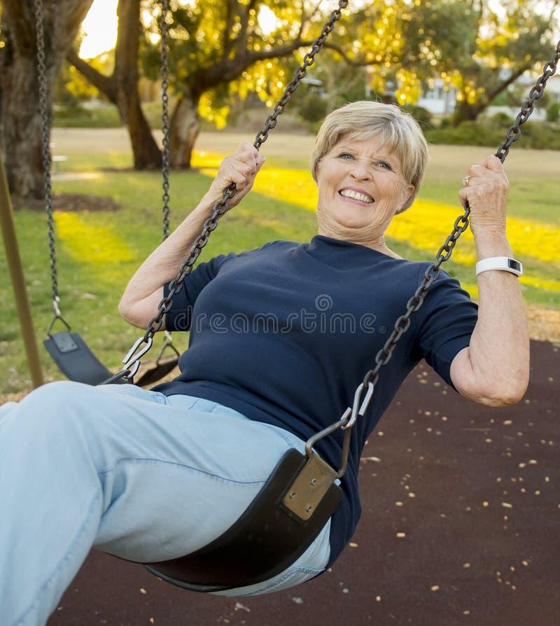 Retrato feliz de la mujer hermosa madura mayor americana en su 70s que se sienta en la sonrisa relajada del oscilación del parque imagenes de archivo