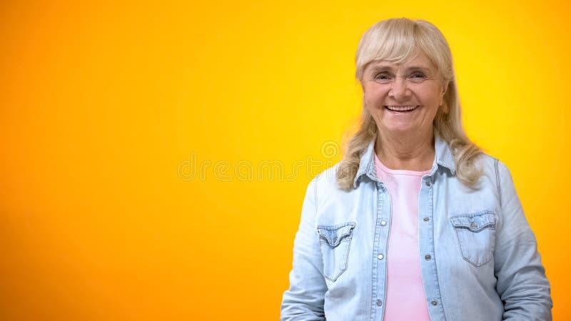 Retrato feliz de la mujer mayor aislado en el fondo brillante, concepto de envejecimiento positivo imágenes de archivo libres de regalías