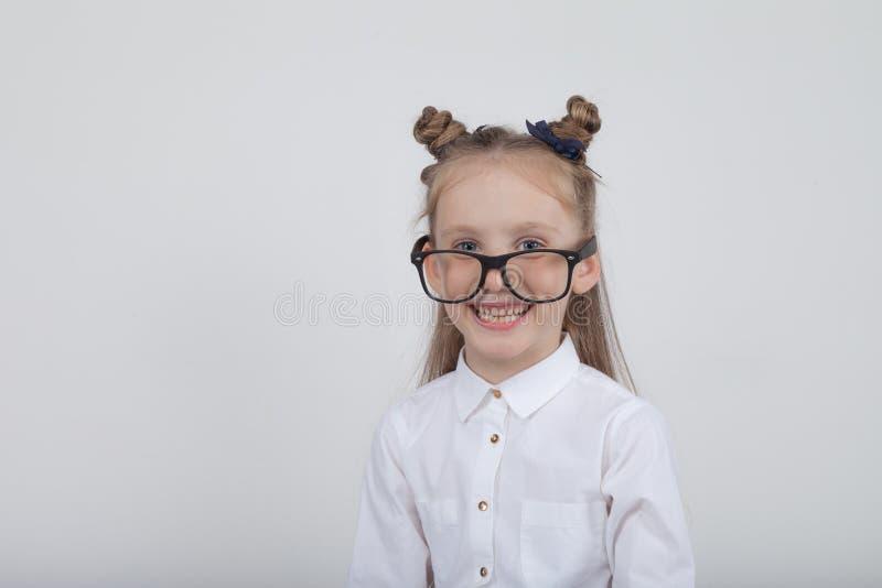 Retrato feliz de la niña, blusa blanca que lleva y lentes negras del marco, oponiéndose al fondo de madera blanco De nuevo a sch imagenes de archivo