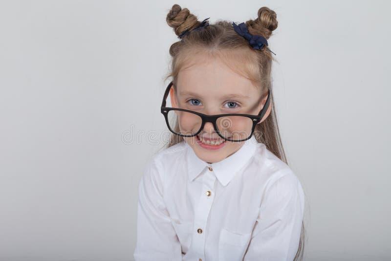 Retrato feliz de la niña, blusa blanca que lleva y lentes negras del marco, oponiéndose al fondo de madera blanco De nuevo a sch fotografía de archivo libre de regalías