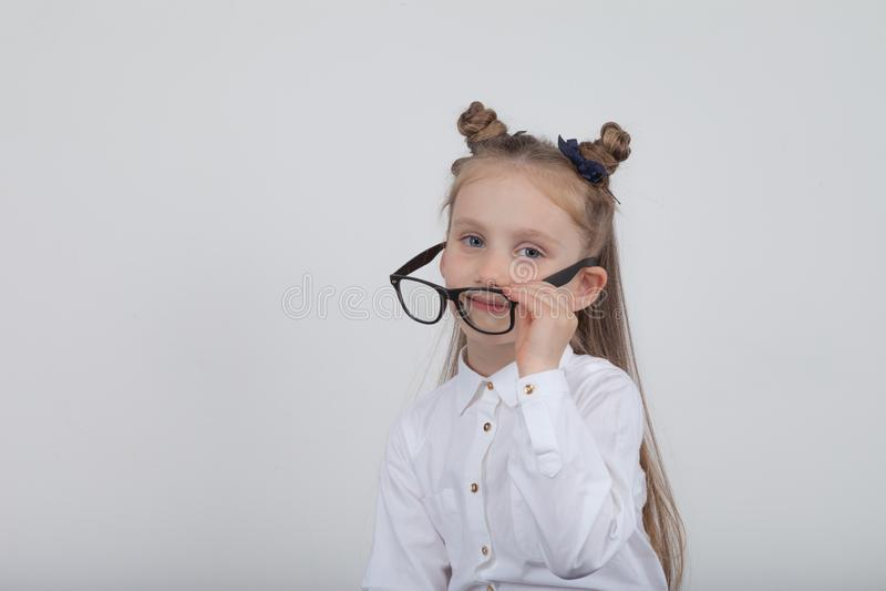 Retrato feliz de la niña, blusa blanca que lleva y lentes negras del marco, oponiéndose al fondo de madera blanco De nuevo a sch fotos de archivo libres de regalías