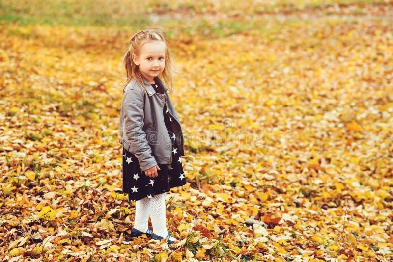 Retrato feliz de la ni?a al aire libre Autumn Time Poco muchacha blondy en capa y vestido de cuero elegantes en el parque del oto fotografía de archivo libre de regalías