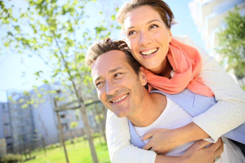Retrato feliz de los pares que se divierten en parque en suburbio imagen de archivo libre de regalías