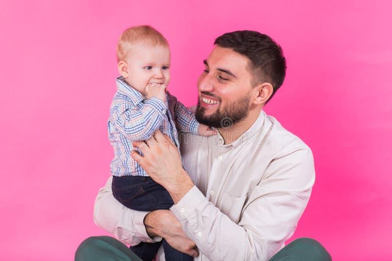 Retrato feliz del padre y del hijo en fondo rosado En estudio foto de archivo