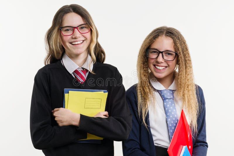 Retrato feliz del primer de los amigos de la High School secundaria Presente en cámara, en uniforme escolar, con los libros y los imágenes de archivo libres de regalías
