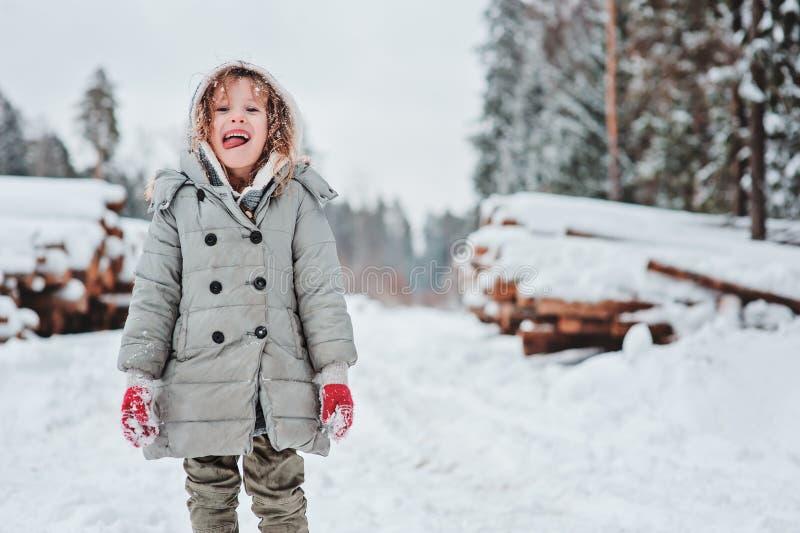 Retrato feliz divertido de la muchacha del niño en el paseo en bosque nevoso del invierno con tala en fondo fotografía de archivo
