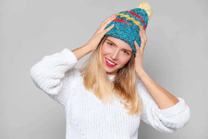 Retrato feliz do estilo de vida da forma da menina do sorriso, chapéu colorido vestindo, no fundo cinzento imagens de stock