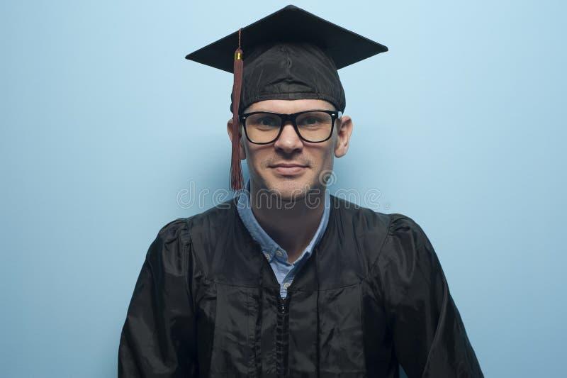 Retrato feliz do estudante do homem novo no chapéu da graduação fotografia de stock