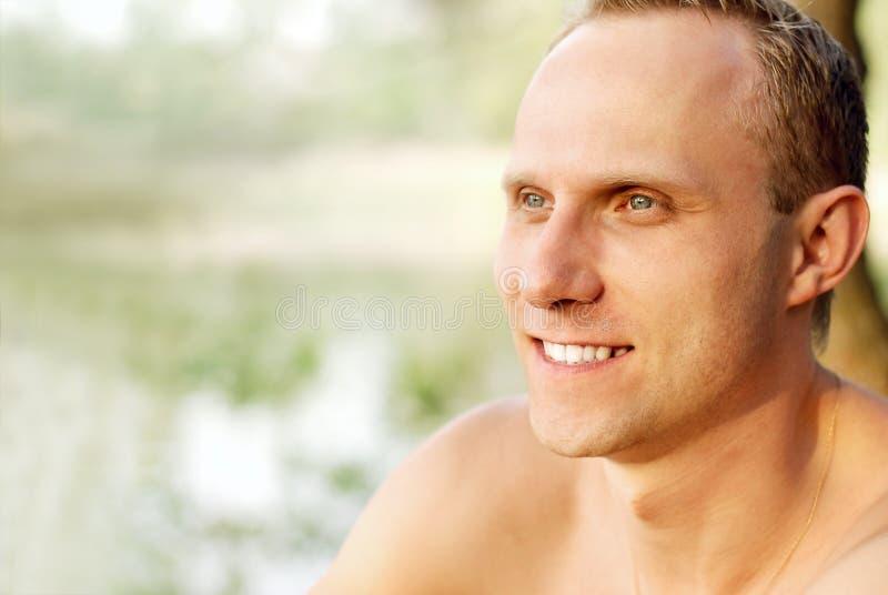 Retrato feliz do homem novo perto do rio imagem de stock royalty free