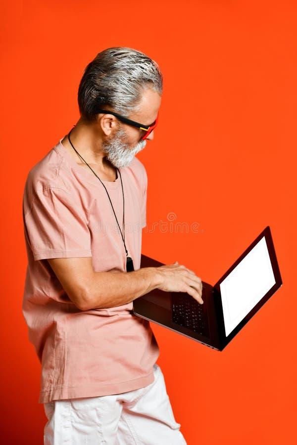 Retrato feliz do pensionista na moda que aprecia o uso do portátil novo imagem de stock royalty free