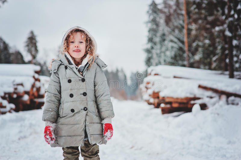 Retrato feliz engraçado da menina da criança na caminhada na floresta nevado do inverno com felling da árvore no fundo imagens de stock