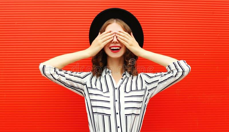 Retrato feliz mulher sorridente cobrindo seus olhos com suas mãos usando camisa branca listrada, chapéu preto redondo sobre a par imagens de stock