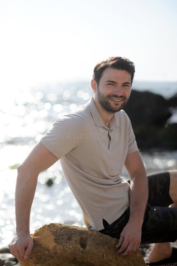 Retrato feliz sonriente del hombre, sentándose en una piedra cerca del océano foto de archivo