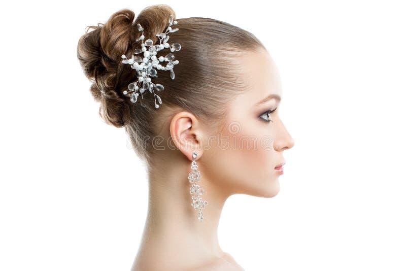 Retrato femenino hermoso en perfil en un fondo blanco Maquillaje y joyería, piel perfecta de la boda imagen de archivo