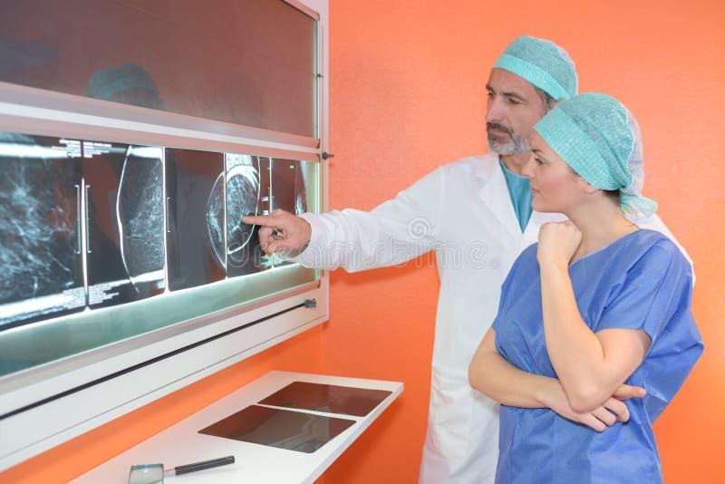 Retrato femenino y doctores de sexo masculino que analizan radiografías fotos de archivo