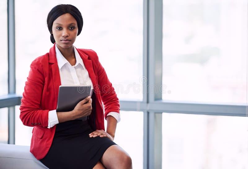 Retrato formal da mulher de negócios preta que guarda uma tabuleta digital imagens de stock royalty free