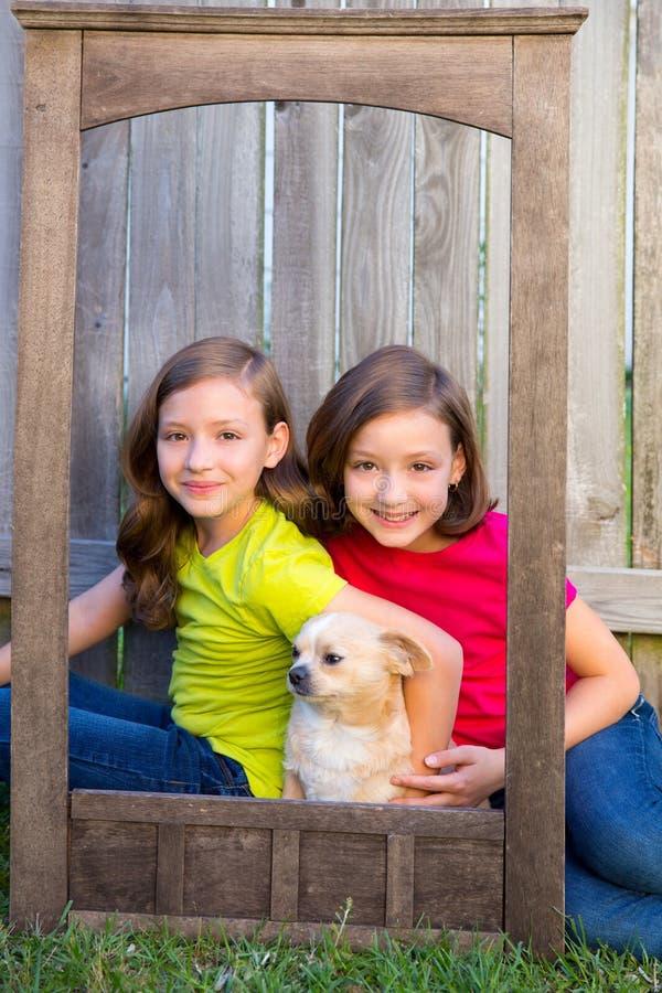 Retrato gemelo de las hermanas con el perro de la chihuahua en marco de madera del grunge imagen de archivo