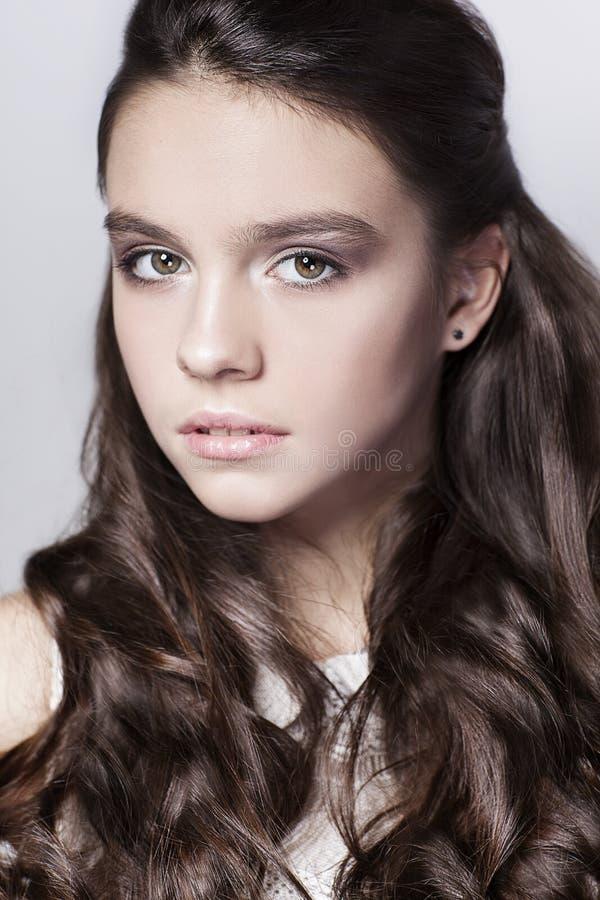 Retrato hermoso de la chica joven con el pelo rizado largo foto de archivo