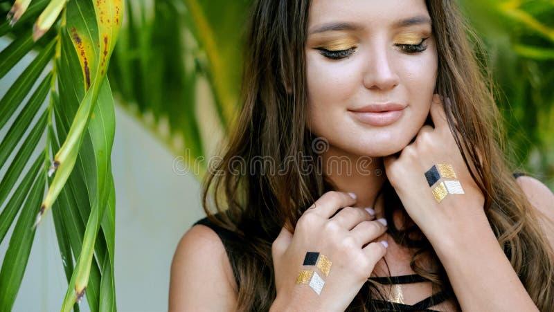 Retrato hermoso de la chica joven con el tatuaje de destello Estilo de la mujer de Boho Maquillaje de oro de las sombras de ojos foto de archivo