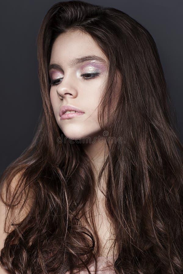 Retrato hermoso de la chica joven con el vestido largo del rosa del ib del pelo rizado en fondo oscuro foto de archivo libre de regalías