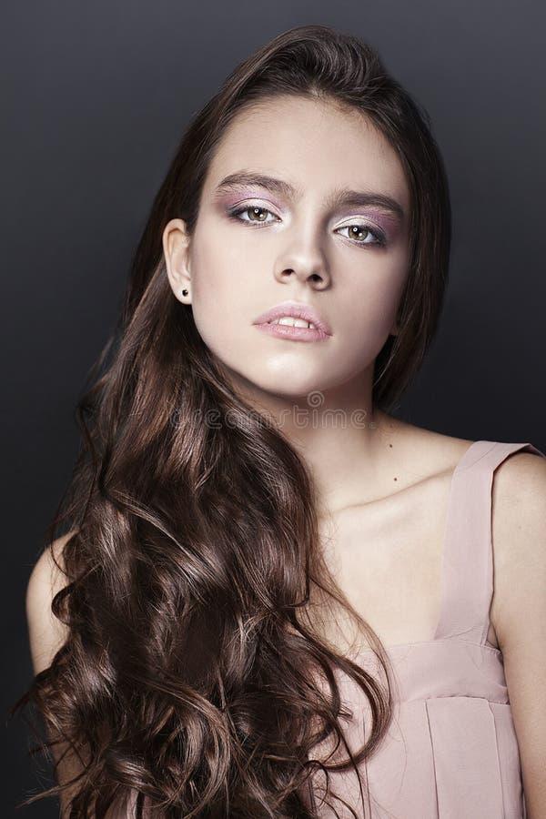 Retrato hermoso de la chica joven con el vestido largo del rosa del ib del pelo rizado en fondo oscuro imagenes de archivo
