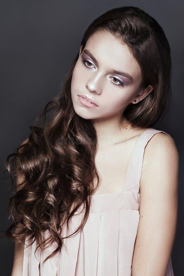 Retrato hermoso de la chica joven con el vestido largo del rosa del ib del pelo rizado en fondo oscuro fotos de archivo libres de regalías