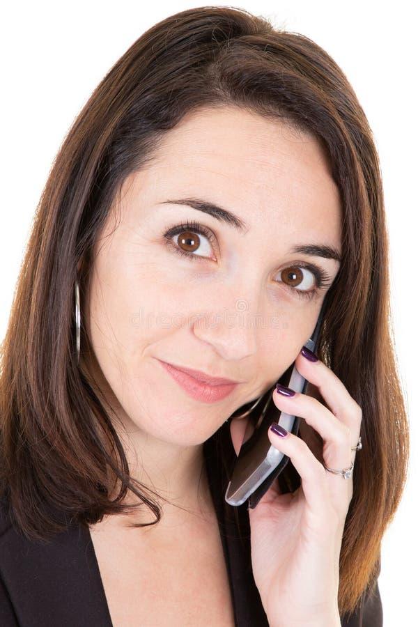 Retrato hermoso de la empresaria que tiene conversación telefónica con el cliente que habla en el teléfono móvil fotografía de archivo