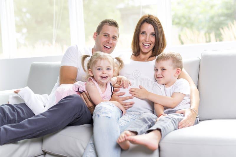 Retrato hermoso de la familia que se sienta en la sala de estar en casa imagen de archivo