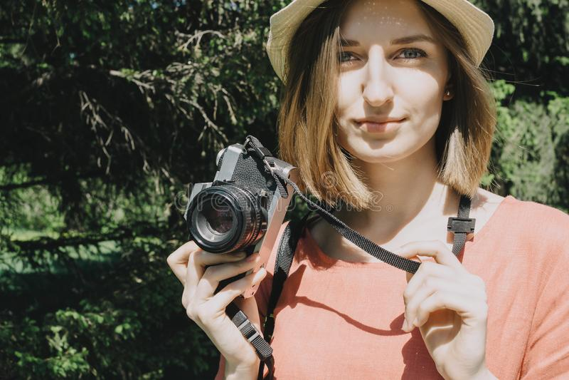 Retrato hermoso de la forma de vida de la mujer adulta joven con la cámara de la película del vintage al aire libre imagenes de archivo
