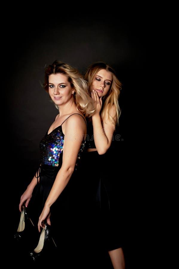Retrato hermoso de la madre y de la hija en estudio en fondo negro Parezca grande Maquillaje profesional Baile y fotos de archivo