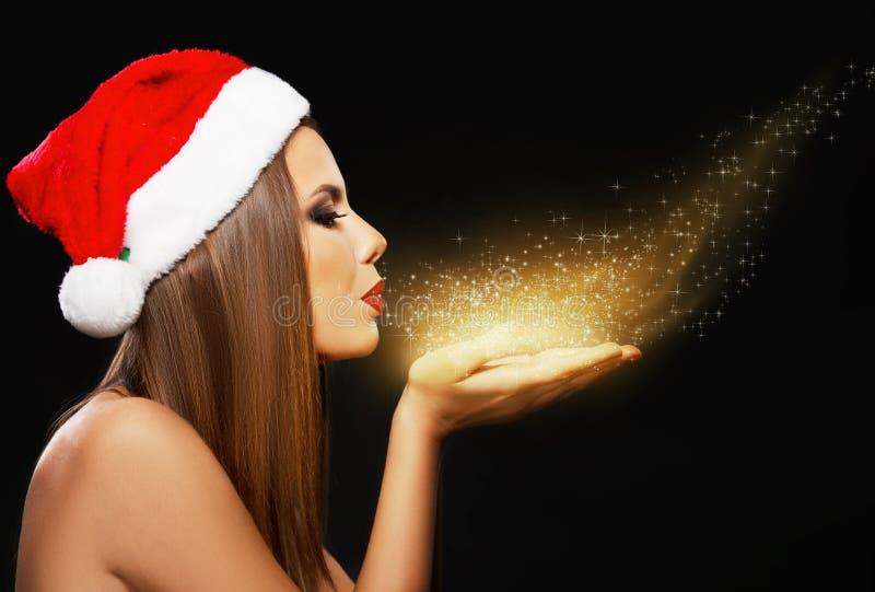 Retrato hermoso de la mujer con el sombrero del ` s de Papá Noel, polvo de oro que sopla imagenes de archivo