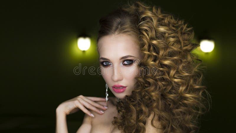 Retrato hermoso de la mujer en fondo negro El encanto compone y pelo rizado largo fotos de archivo