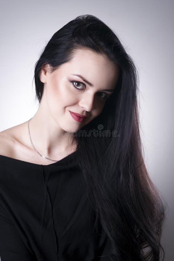 Retrato hermoso de la mujer en un fondo gris El profesional hace foto de archivo