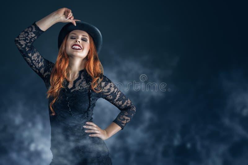 Retrato hermoso de la mujer vestido como bruja para el partido de Halloween foto de archivo