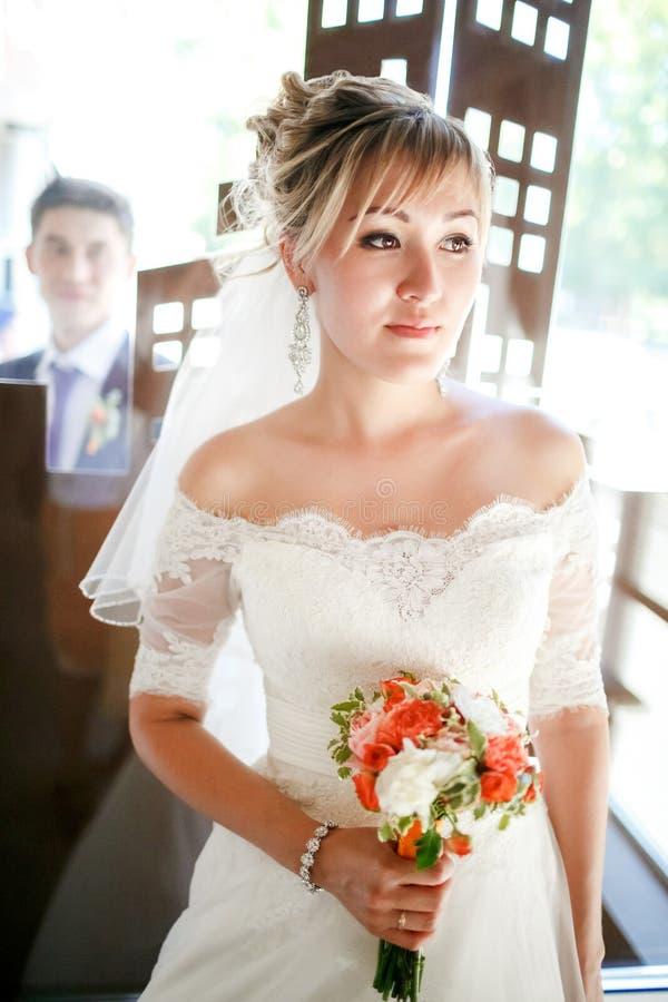 Retrato hermoso de la novia con el novio detrás del vidrio, casandose el ramo en manos dentro imagen de archivo libre de regalías