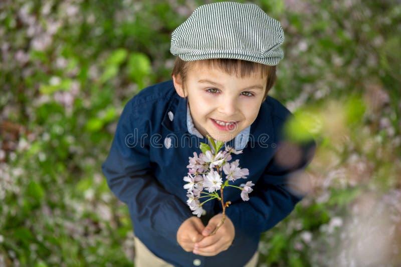 Retrato hermoso de un niño preescolar joven que sostiene la flor foto de archivo libre de regalías