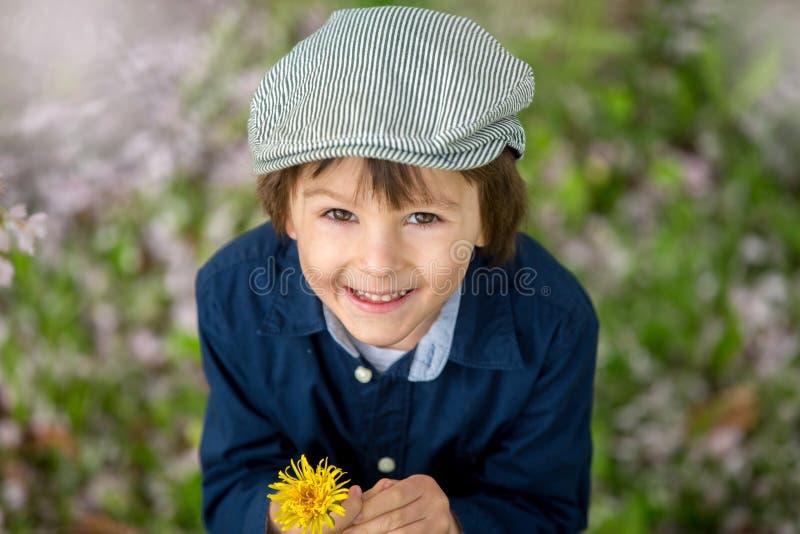 Retrato hermoso de un niño preescolar joven que sostiene la flor fotografía de archivo libre de regalías