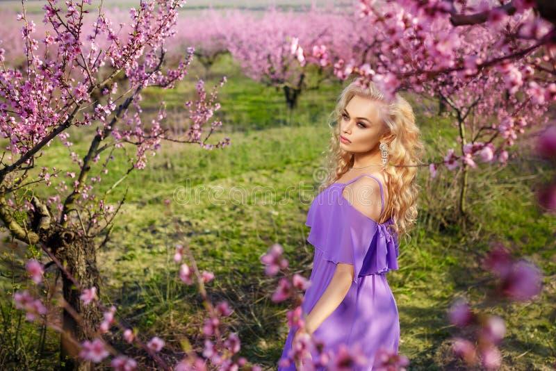 Retrato hermoso de una muchacha en el jardín floreciente de la primavera, día soleado, jardín del melocotón foto de archivo libre de regalías