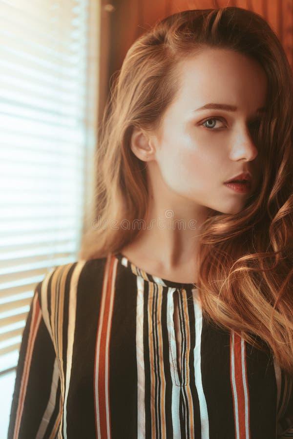 Retrato hermoso de una muchacha en perfil Soporte de la muchacha cerca de la ventana con las persianas Retrato hermoso de una muc imágenes de archivo libres de regalías