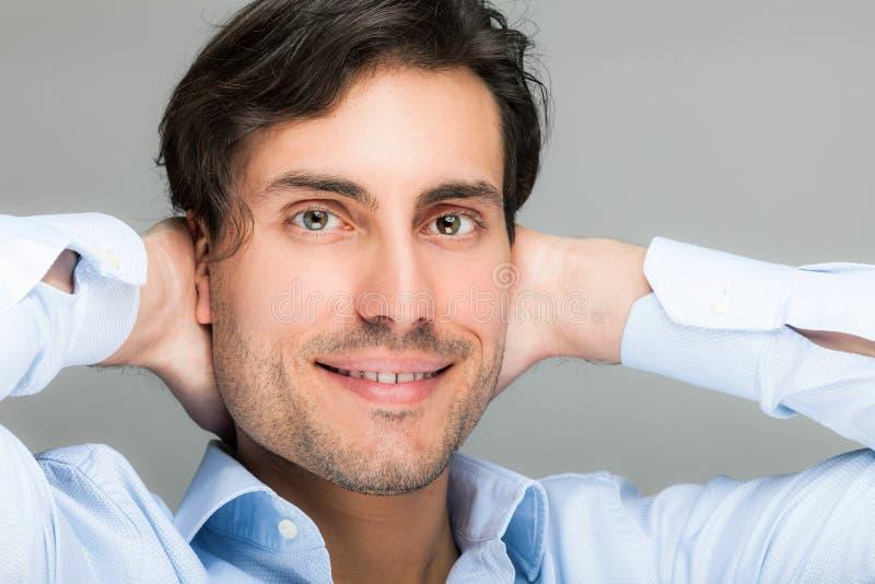 Retrato hermoso del hombre con sus manos detrás de su cabeza imagenes de archivo