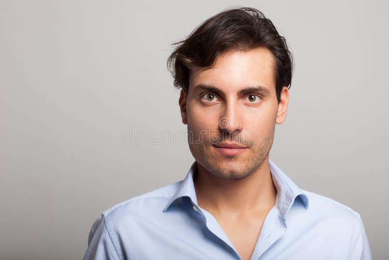 Retrato hermoso del hombre en fondo gris imagenes de archivo