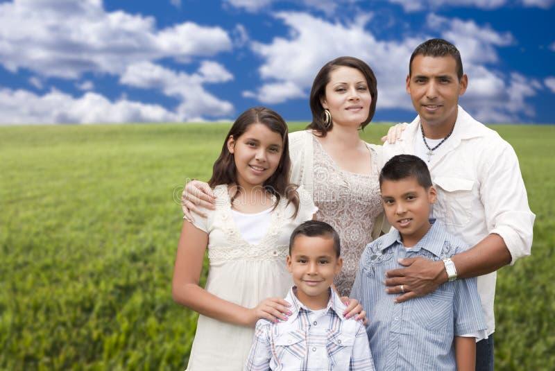 Retrato hispánico de la familia que se coloca en campo de hierba fotografía de archivo libre de regalías