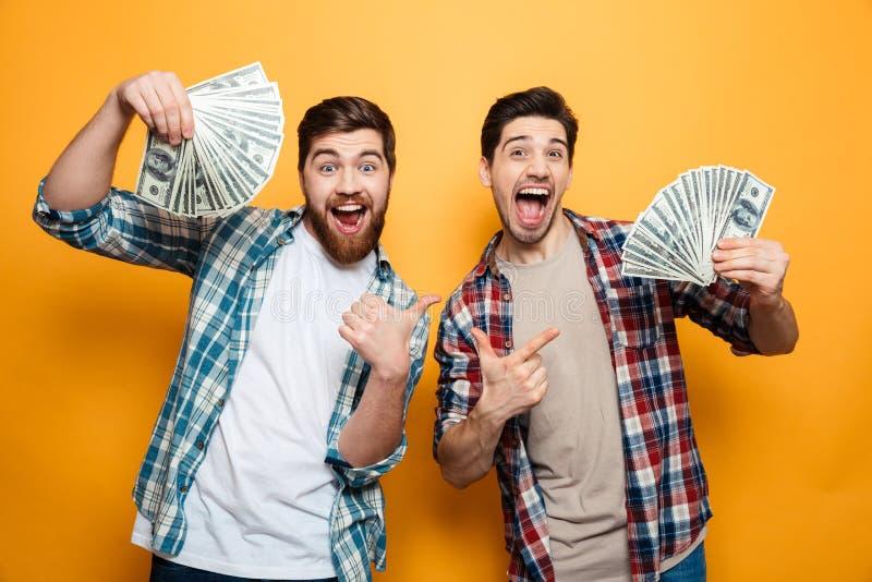 Retrato hombres emocionados de dos de un oung que muestran el dinero fotografía de archivo libre de regalías
