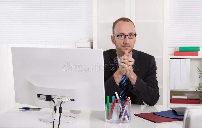 Retrato: Homem de negócios que senta-se em seu escritório com terno e laço imagens de stock royalty free