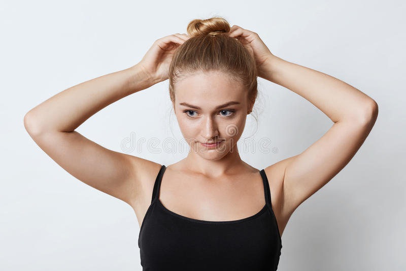 Retrato horizontal da fêmea atrativa com nó do cabelo louro, olhando pensativamente para baixo com seus olhos azuis ao tentar faz fotografia de stock royalty free