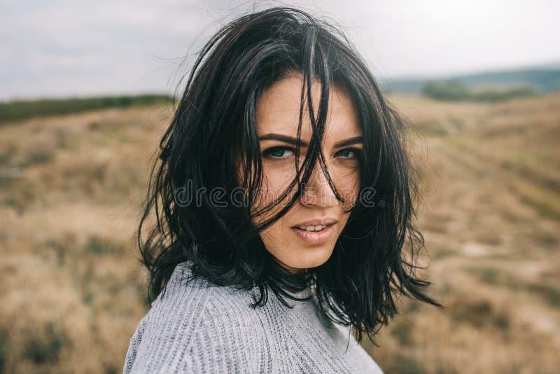Retrato horizontal da mulher moreno romântica que levanta contra a natureza, fundo do prado com cabelo ventoso Povos e estilo de  imagens de stock